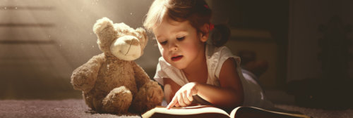 a little girl with her teddy bear reading a book