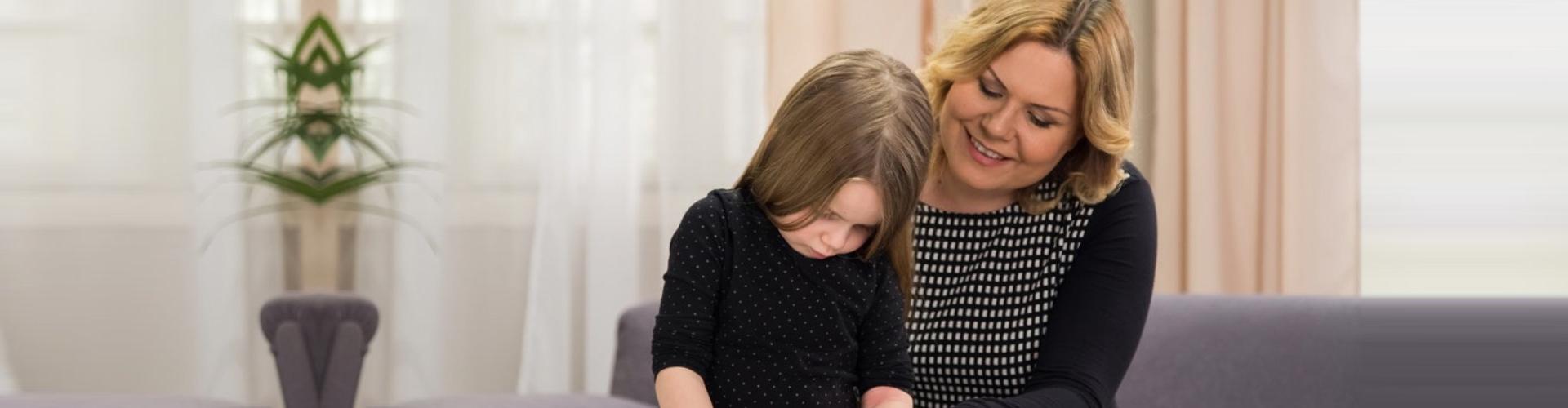 caregiver teaching a little girl